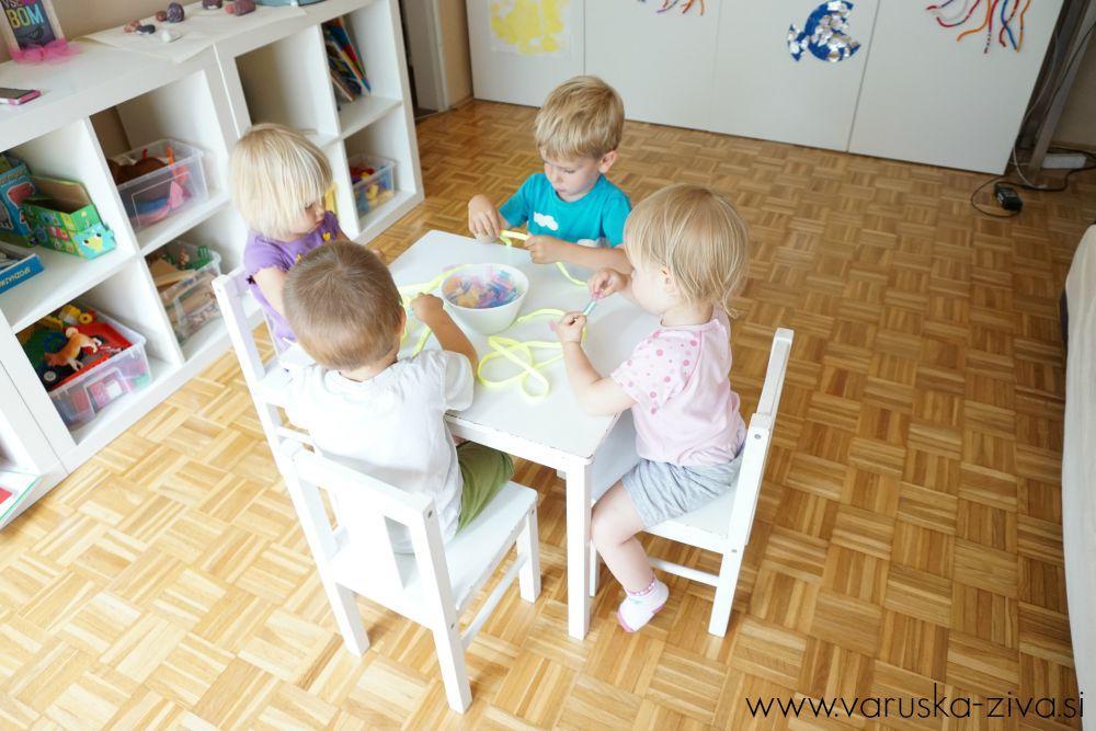 Otroci izdelujejo verižice iz slamic