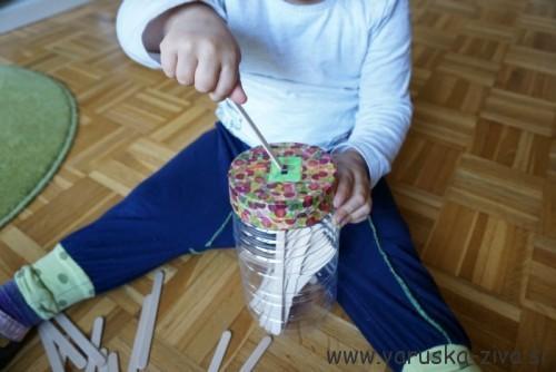 Vstavljanje palčk v posodico - doma izdelane igrače
