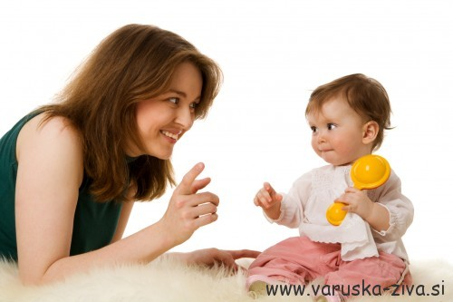 Mother playing with one year daughter isolated on white